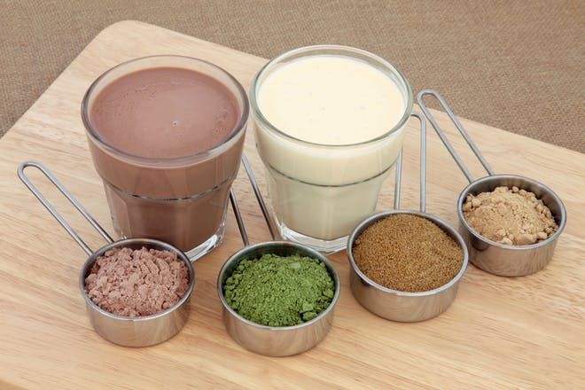 Two protein shakes alongside food powder supplements from left to right: chocolate whey, wheat grass, pomegranate and maca root.