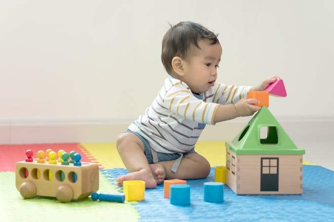 Eight-month old baby boy playing with wooden toys