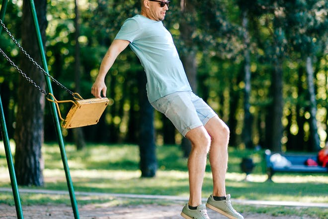 Funny man misjudging jumping of swing