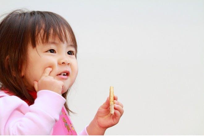 little girl eating rice cracker