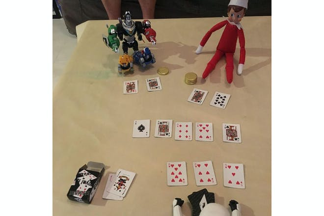 Elf on the shelf playing poker with cards