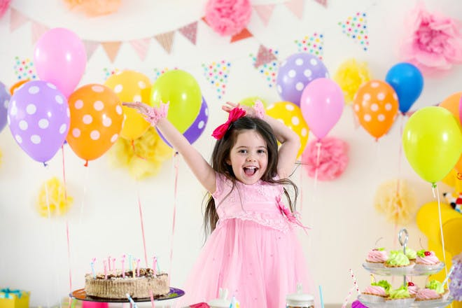 happy girl in pink dress with arms up with balloons behind her