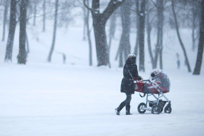 Mum pushing pram alone in snow