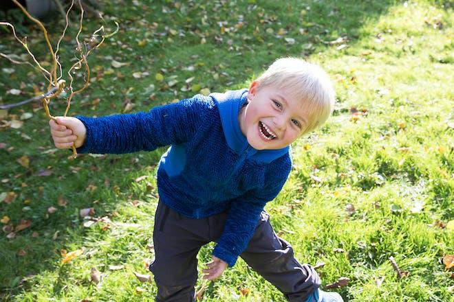 little boy holding twig in garden