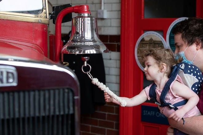 Girl ringing fire engine bell