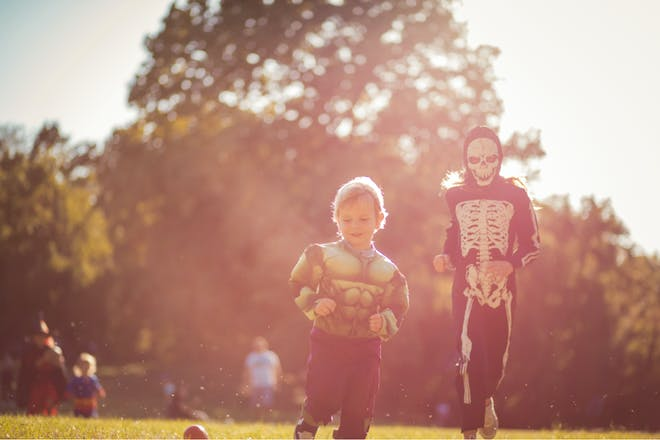 A toddler wearing a Hulk Halloween costume and a taller child wearing a skeleton costume race through a park