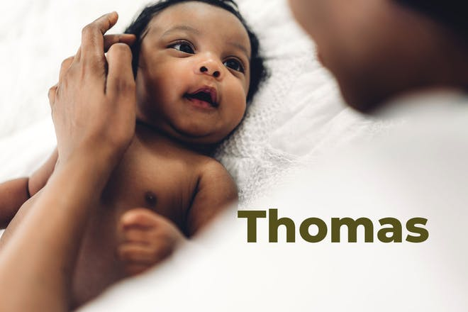 Mum stroking baby's hair as he lies on bed. Name Thomas written in text