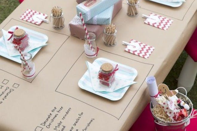 Christmas table laid for children with tasks, presents and pencils
