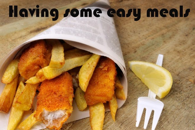 fish and chips wrapped in newspaper on wooden table
