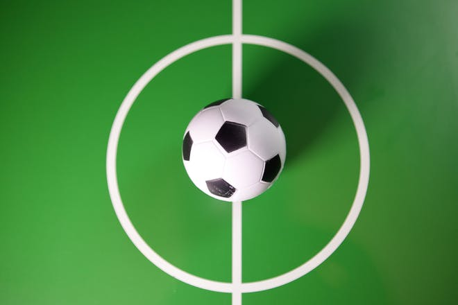 Mini toy football on a green pitch background