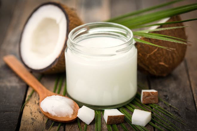 Jar of solid coconut oil with spoon, coconut halves and coconut pieces