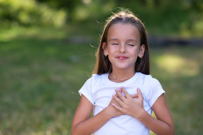 Girl with hands on heart standing outside
