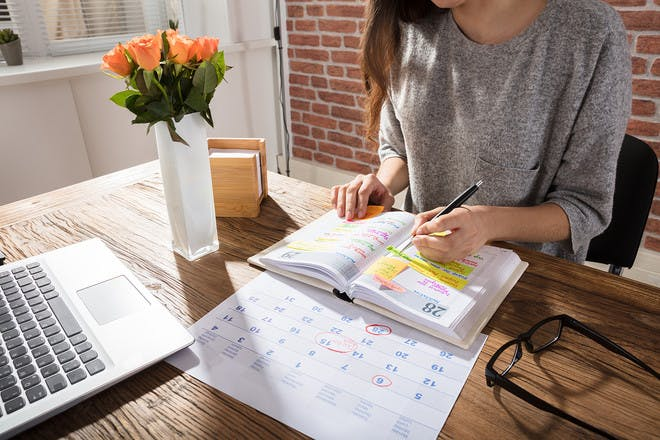 Woman writing in diary on desk