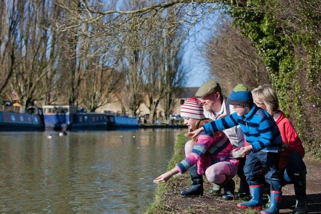 family feeding ducks at a canal