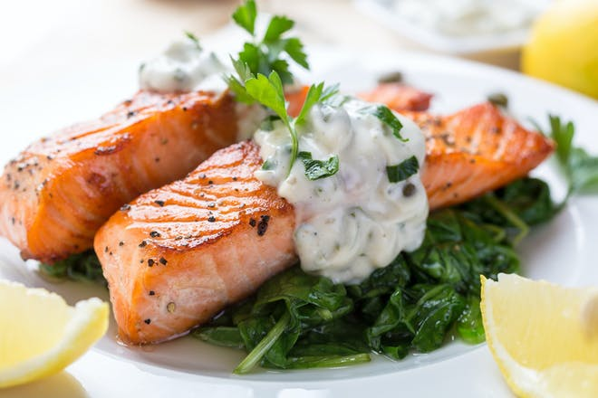 Grilled salmon with tartar sauce, spinach and lemon wedges.