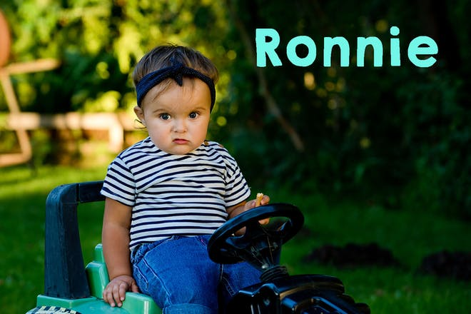 Baby girl sitting on toy tractor, text says Ronnie