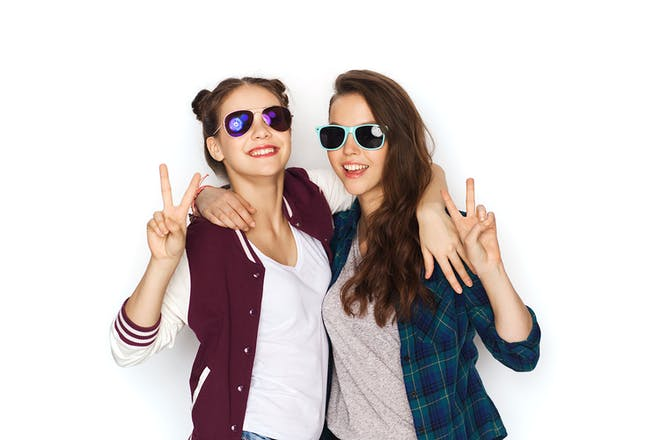Two teenage girls wearing sunglasses and making peace signs