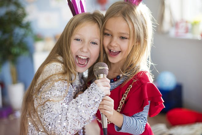 two young girls dressed up in adult's sparkly clothes singing in microphone