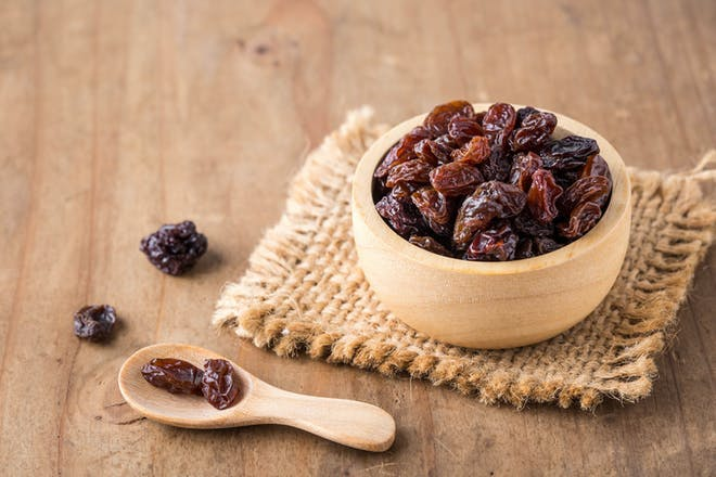 Wooden bowl of raisins with scoop