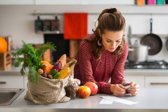 Woman in kitchen with shopping looking at receipt