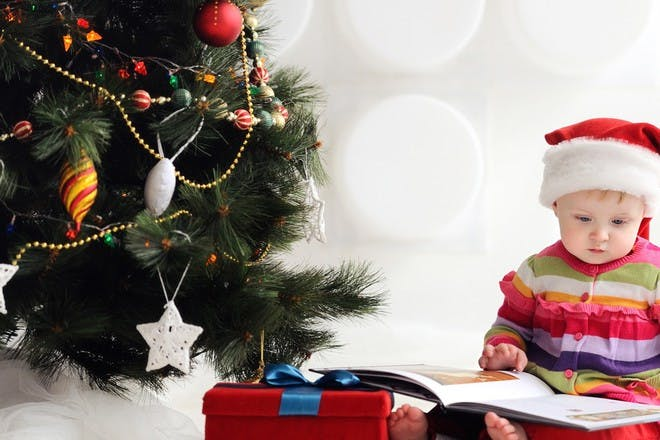 baby next to christmas tree with book