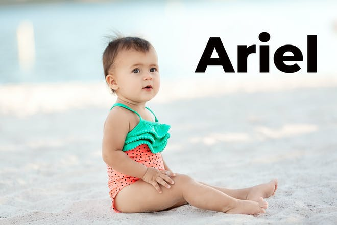 Baby girl sat on the sand with the word Ariel in black font