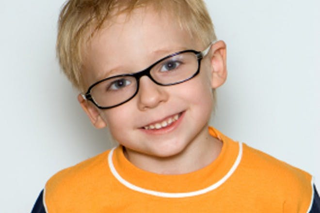 boy in yellow shirt and glasses smiling