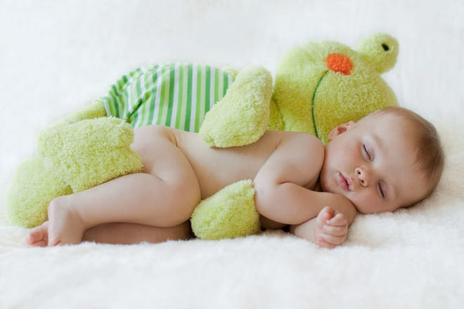 Baby sleeping with cuddly toy