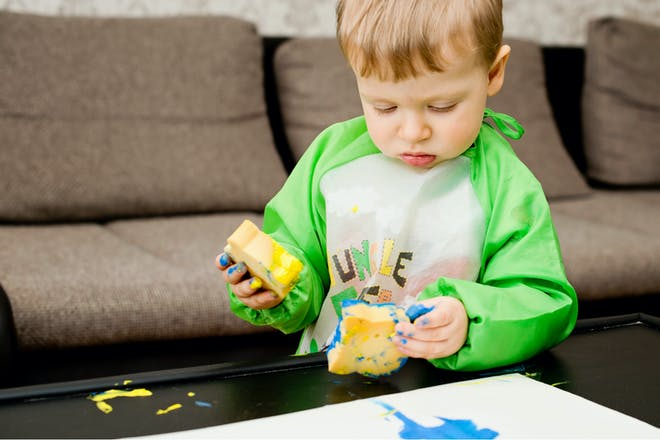 Little boy painting with sponges