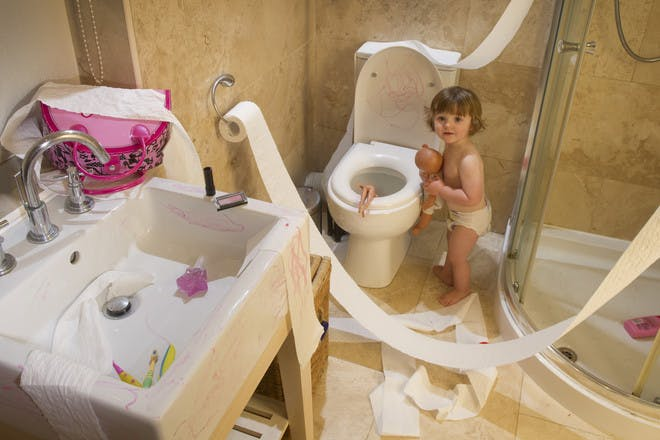 baby in messy bathroom with toilet roll everywhere