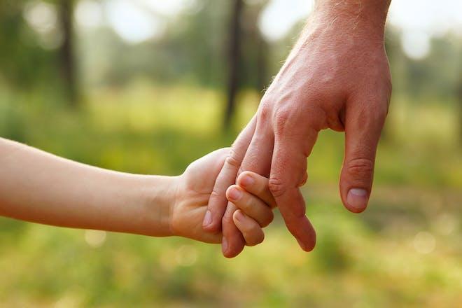 Dad holding child's hand