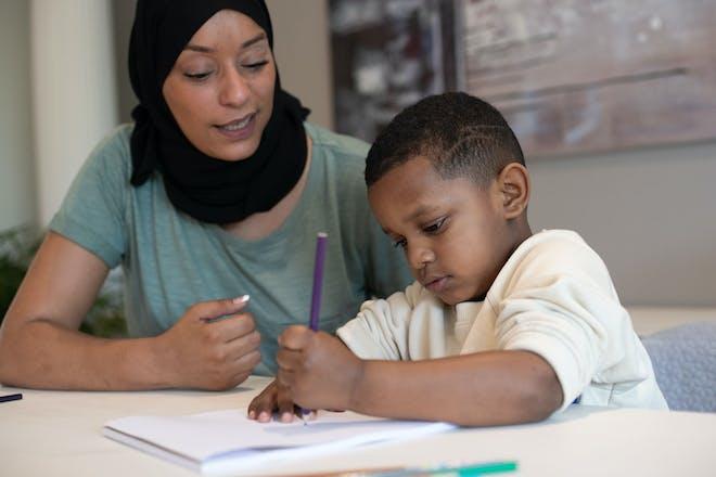 Mum helping child write
