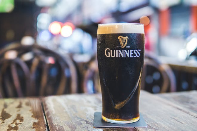 A pint of Guinness on a table.