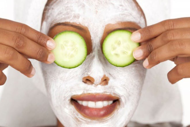 woman wearing face mask with cucumber slices over eyes