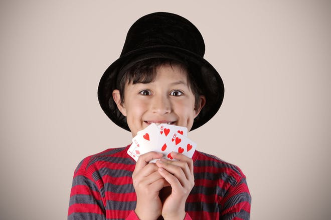 Boy wearing magicians hat and holding cards