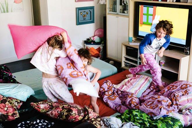 Kids pillow fighting in living room