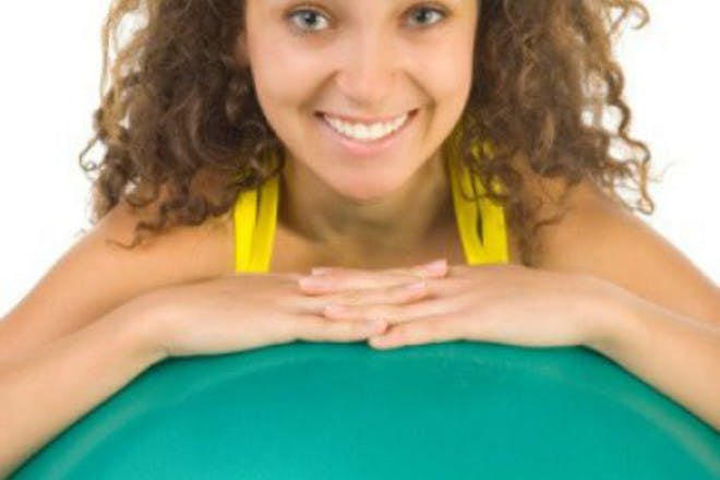 smiling woman leaning on exercise ball