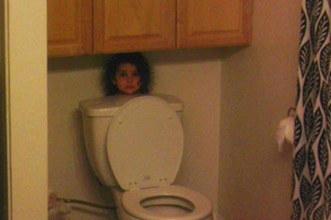 child hiding behind toilet