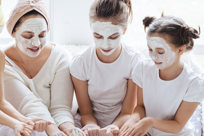 mum and daughters wearing face masks and looking at manicure