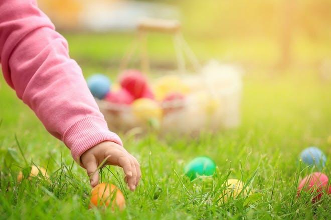 Girl picking Easter eggs in grass