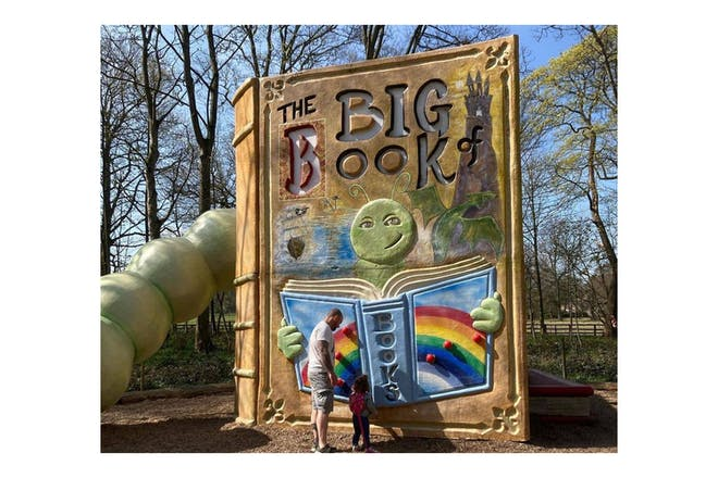 Toddler and dad looking at a large statue of a book