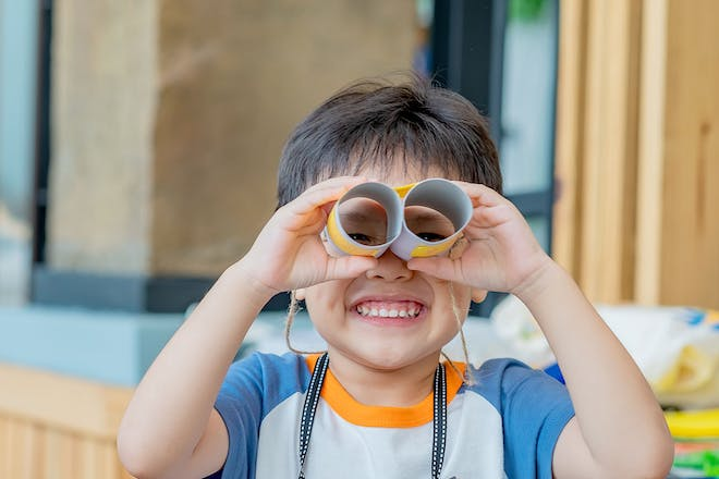 Young boy with binoculars made from toilet rolls