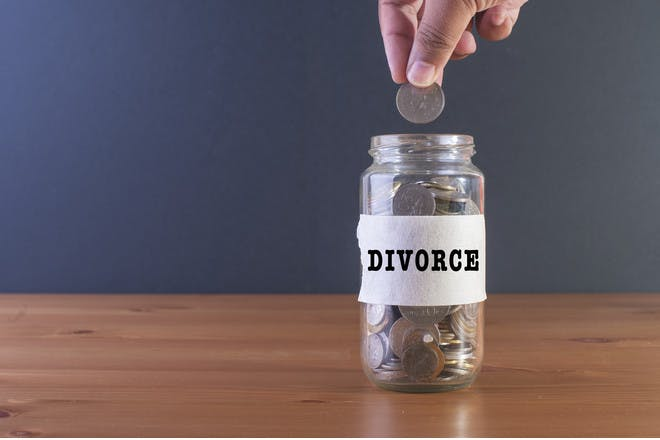Hand dropping coin in jar labelled divorce
