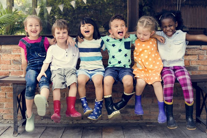 Diverse group of children from different ethnic backgrounds sitting on a bench outdoors