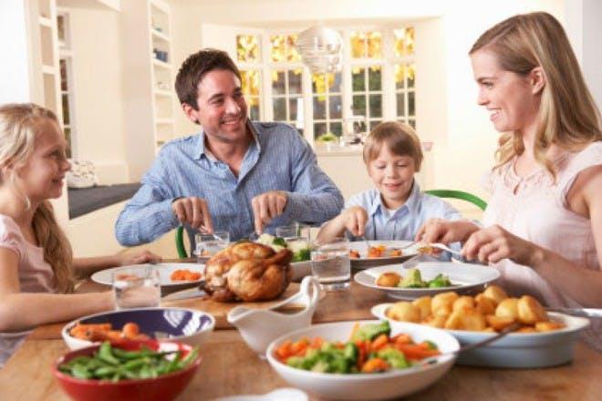 family sitting at table eating dinner