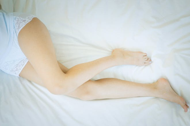 A woman lying on a bed wearing cotton underwear