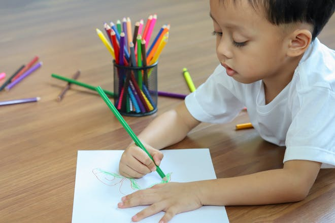Toddler draws a monster on a sheet of paper next to a pot of coloured pencils