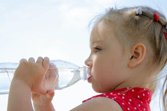 Little girl drinking from a water bottle
