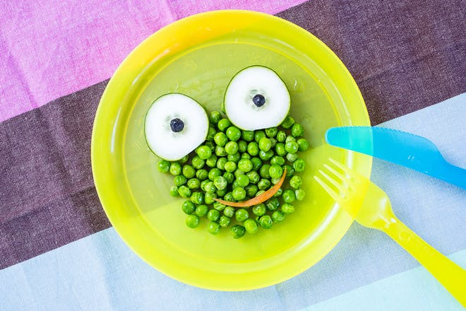 Bowl of peas with cucumber for eyes and a carrot smile so looks like a frog