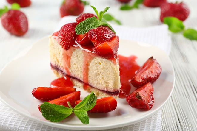 Slice of strawberry cheesecake on a white plate